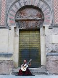 A woman playing a Spanish Flamenco Guitar in front of Mosque Cathedral of Cordoba Stock Photo