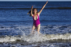 Woman playing and splashing in the ocean royalty free stock photo