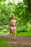 Woman playing sports, running in the park Royalty Free Stock Photos