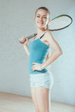 Woman playing squash. Girl standing in the court, holding a racket and a cute smiling Royalty Free Stock Images