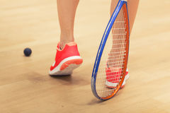 Woman playing squash. A young squash player,squash court Royalty Free Stock Photography