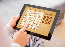 Woman playing Sudoku on tablet computer Royalty Free Stock Photos