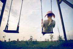 Woman playing on a swing at sunset Stock Images