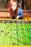 Woman playing table football game Stock Image
