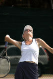 Woman playing tennis. Young attractive woman serving tennis, dark area for copy Royalty Free Stock Image