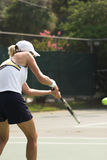 Woman playing tennis. Young woman returning serve in tennis Royalty Free Stock Photos