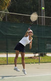 Woman playing tennis. Woman returning difficult tennis shot Royalty Free Stock Image