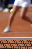 Woman playing tennis. A female tennis player on clay court, the focus on the ball above the net Stock Photos