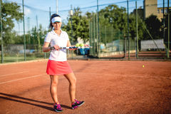 Woman playing tennis on clay court with tennis racket, balls and white outfit Stock Photos