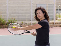 Woman playing tennis on the court Royalty Free Stock Photos