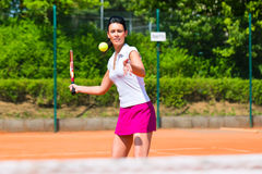 Woman playing tennis on court outdoors Stock Image