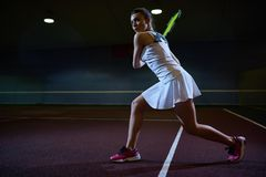 Woman Playing tennis in Dark Court Stock Photography