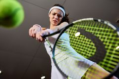 Woman Playing Tennis Low Angle. Low angle portrait of forceful woman playing tennis in indoor court, focus on tennis racket hitting ball, copy space Royalty Free Stock Photography