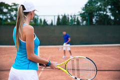Woman playing in tennis with man outdoors Royalty Free Stock Photography