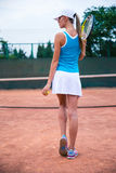 Woman playing in tennis outdoors. Back view portrait of a young woman playing in tennis outdoors royalty free stock image