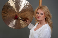 Woman playing tibetan gong in photo studio on grey studio background. Stock Image