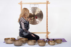 Woman playing tibetan gong in photo studio on white background. Royalty Free Stock Photography