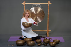 Woman playing tibetan singing bowl in photo studio on grey studio background. Royalty Free Stock Images