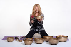 Woman playing tibetan singing bowl in photo studio on isolated white studio background. Stock Photo