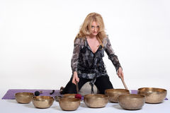Woman playing tibetan singing bowl in photo studio on isolated white studio background. Stock Photography