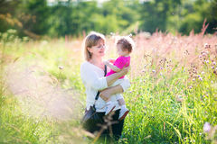 Woman playing with a toddler girl in sunny  field. Beautiful women playing with a toddler girl in a sunny summer field Royalty Free Stock Photo