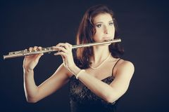Woman playing transverse flute on black. Music and elegance. Alluring elegant woman playing on transverse flute. Female musician with her instrument performing Stock Photo