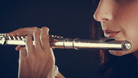 Woman playing transverse flute on black. Royalty Free Stock Images