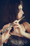Woman playing transverse flute on black. Music and elegance. Alluring elegant woman playing on transverse flute. Female musician with her instrument performing Royalty Free Stock Photos