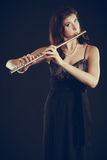 Woman playing transverse flute on black. Royalty Free Stock Photography