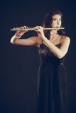 Woman playing transverse flute on black. Stock Image