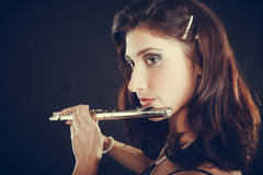 Woman playing transverse flute on black. Stock Photography