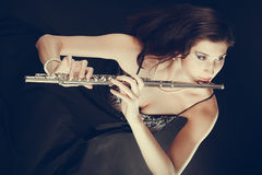 Woman playing transverse flute on black. Royalty Free Stock Photo