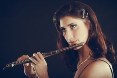 Woman playing transverse flute on black. Music and elegance. Alluring elegant woman playing on transverse flute. Female musician with her instrument performing Royalty Free Stock Photo