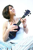 Woman playing ukulele stock image