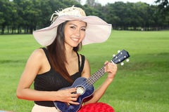 Woman playing ukulele Stock Images