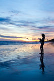 Woman playing ukulele on sunset beach Stock Images