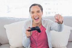Woman playing video games on sofa and winning Royalty Free Stock Image