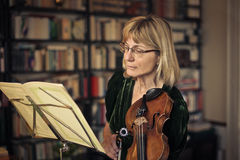 Woman playing the violin stock images