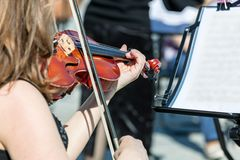 Woman playing violin during classical music concert. On the street stock photography
