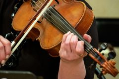 Woman playing the violin. Female fingers grip the strings and hold the bow. Close-up. Shallow depth of field. Selective focus. royalty free stock photos