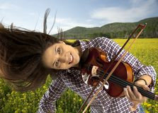 Woman playing violin. On on field background Stock Photography