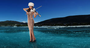 Woman playing a violin on a frozen lake Stock Photos