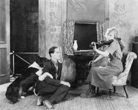 Woman playing the violin for her boyfriend and dog Royalty Free Stock Photo