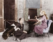 Woman playing the violin for her boyfriend and dog royalty free stock image