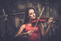 Woman playing violin in mystic interior Stock Images