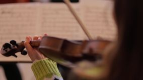 Woman playing the violin on the notes. stock footage