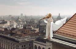 Woman playing the violin on the top of the edge of the roof Royalty Free Stock Image