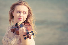 Woman playing violin on violin near beach Royalty Free Stock Photo