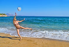 Woman playing volleyball at a greek beach Royalty Free Stock Photos