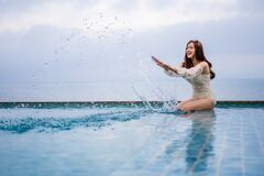 Free Woman Playing Water Splash In Swimming Pool With Sea Background Stock Photo - 207910200